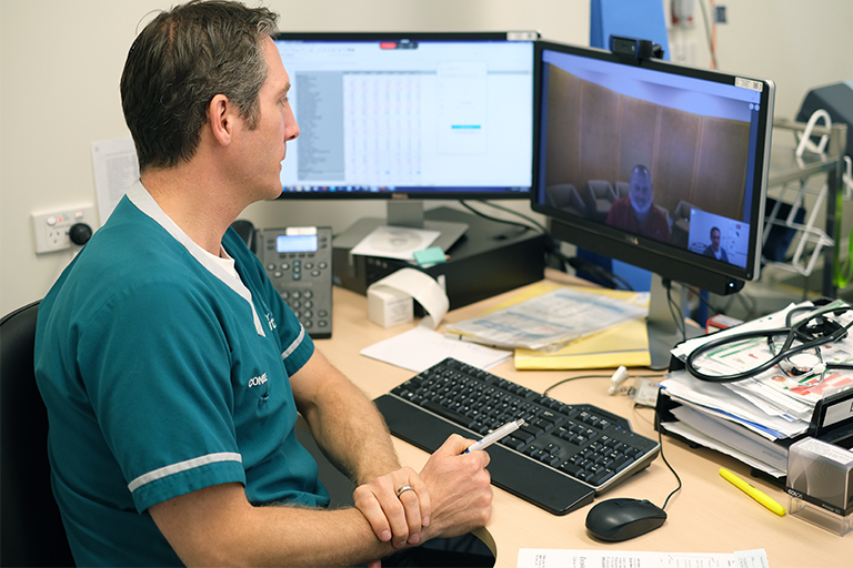 : A male health professional sits in front of computer and conducts an online conversation with two other people who are visible on the computer screen.