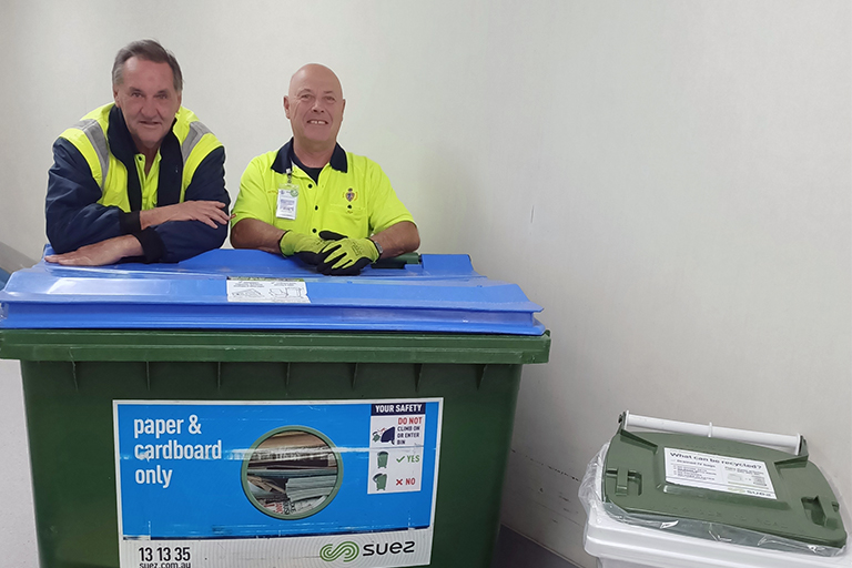 Two men wearing high visibility clothing lean against a large paper and cardboard recycling bin.