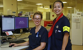 Two female nurses wearing Fremantle Hospital uniforms stand next to two computer screens.