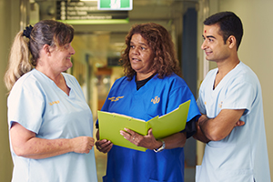A male and two female support staff members in conversation in a hospital corridor