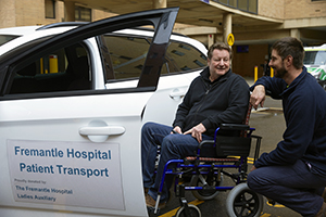 A man kneels down next to a man in a wheelchair. They are beside a car and a sign on the door reads 'Fremantle Hospital Patient Transport'