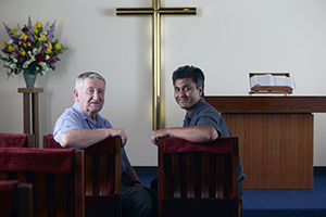 Two men seated in a chapel.