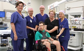 A young man in a wheelchair and a woman stand in a hospital theatre with four female theatre staff.