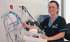 A female nurse stands beside medical equipment.
