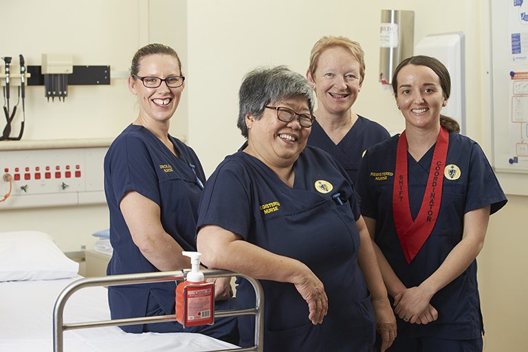 Four female nurses in Fremantle Hospital uniforms standing next to a hospital bed.