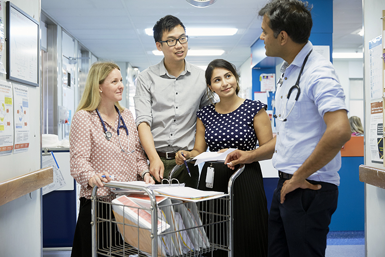 Four male and female health professionals talking in a hospital corridor