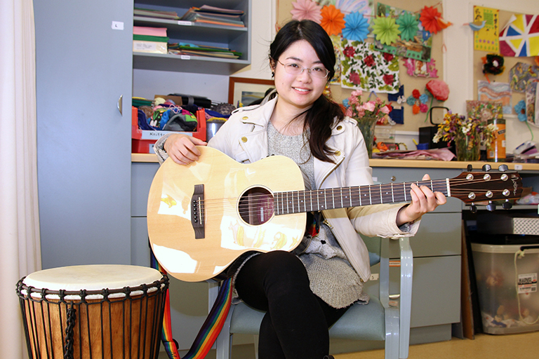 A young woman seated in a chair holds a guitar. A drum is next to the chair.