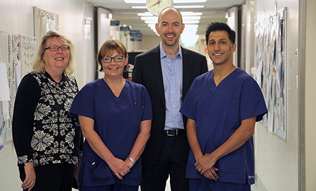 Four health professionals stand in a hospital corridor