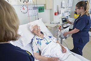 An older female patient is in a hospital bed. A female nurse stands beside the bed.