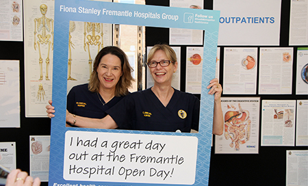 Two female nurses hold a cut out frame in front of them that reads 'I had a great day at the Fremantle Hospital Open Day'.