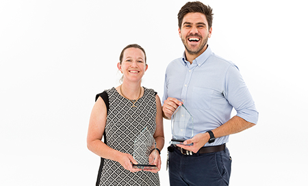 A woman and a man stand beside each other. Each is holding a small glass trophy.